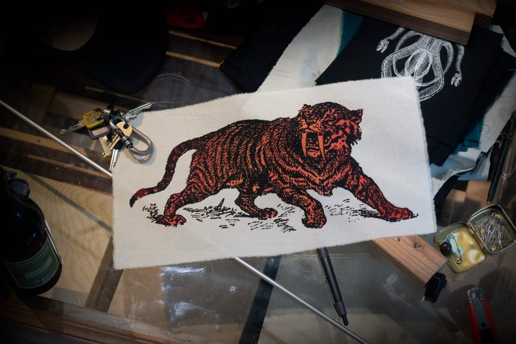 Sabre Tooth Tiger Red Orange Screenprint Back Patch on table with objects