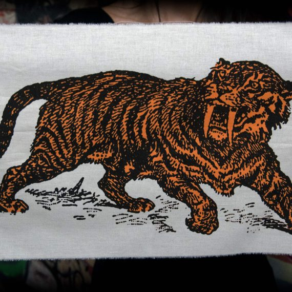 Sabre Tooth Tiger Orange Screenprint Back Patch held by hands