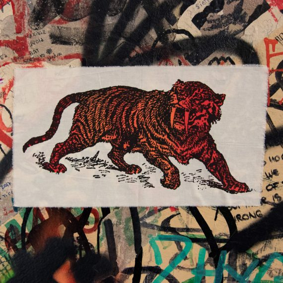 Sabre Tooth Tiger Red Orange Screenprint Back Patch on graffiti wall