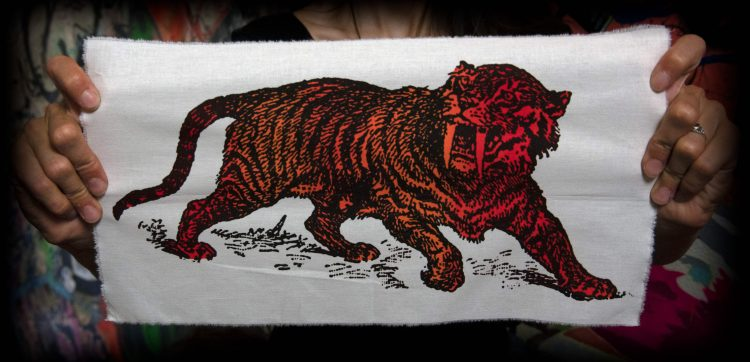 Sabre Tooth Tiger Red Orange Screenprint Back Patch held by hands